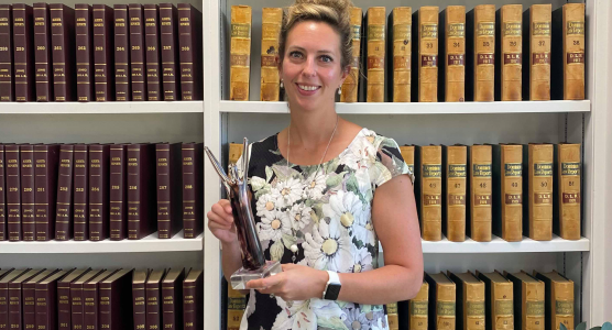 Kerry Gellrich holding AACE Business Excellence Award in front of law bookshelf